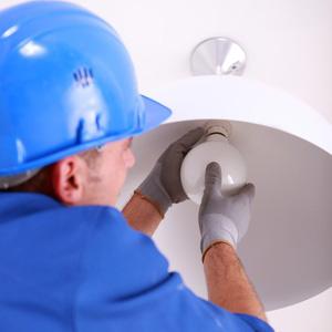 Electrician replacing light bulb